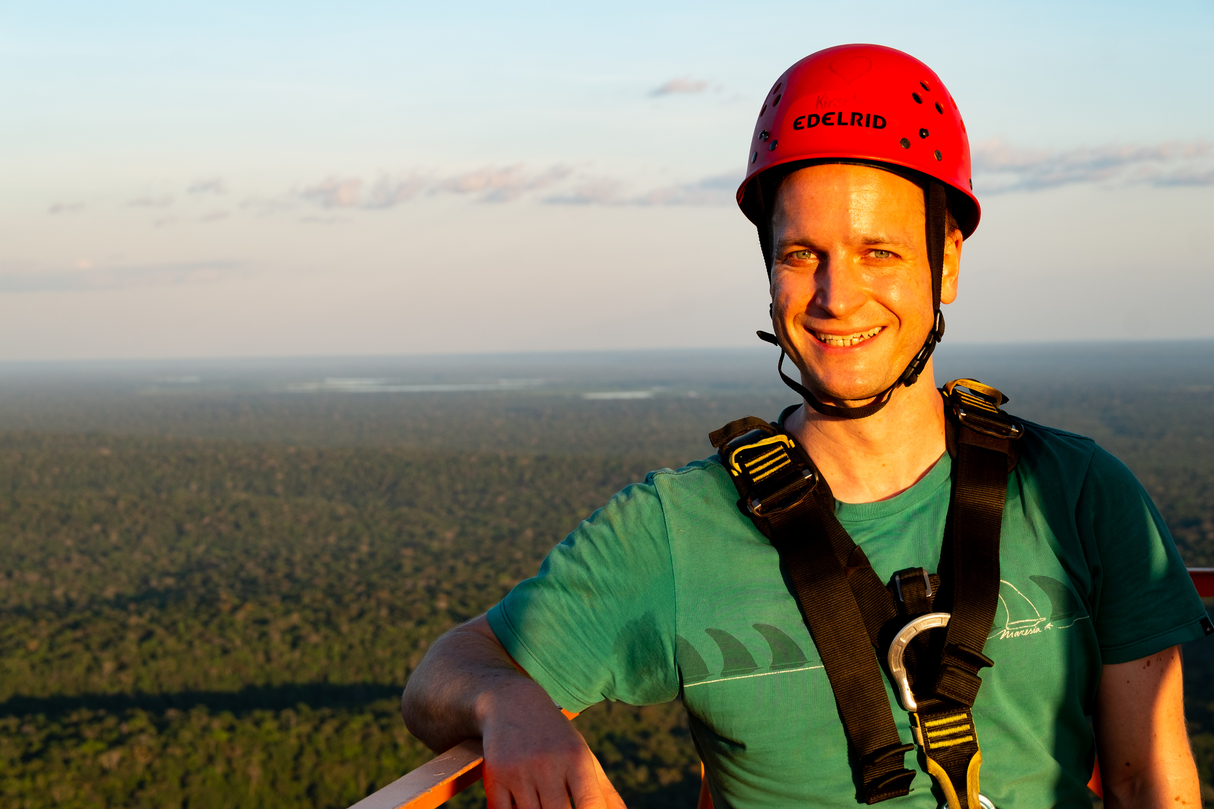 Stefan Wolff stands atop the ATTO tall tower in the warm glow of the evening sun. Behind him the Amazon rainforest strechtes to the horizon. You can see the Uatuma river glinting in the distance between the trees.