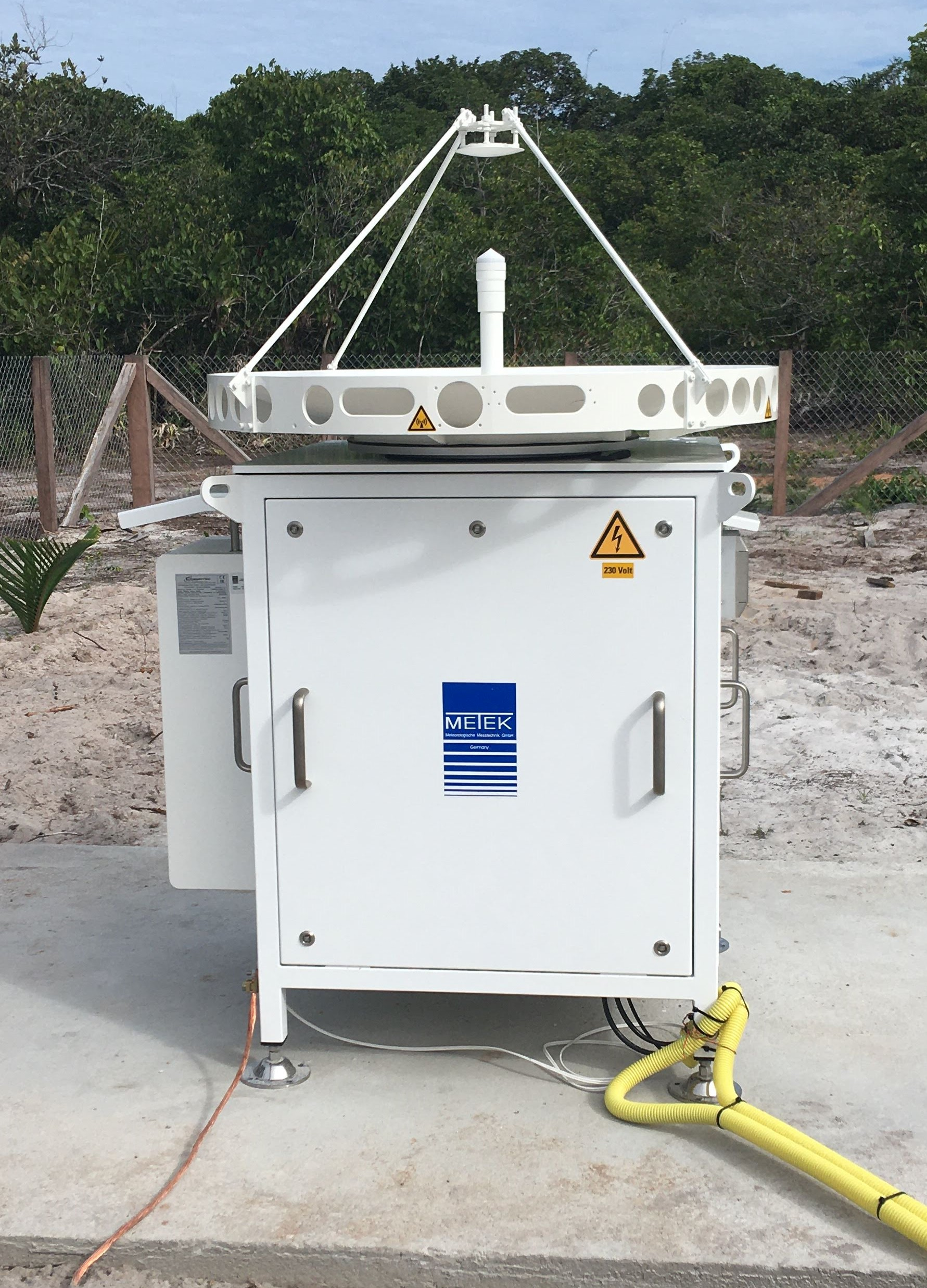 Closer view of the MIRA radar with the antenna and the small container. Inside the yellow tubes are several cables that connect the radar to the research container and the power source.